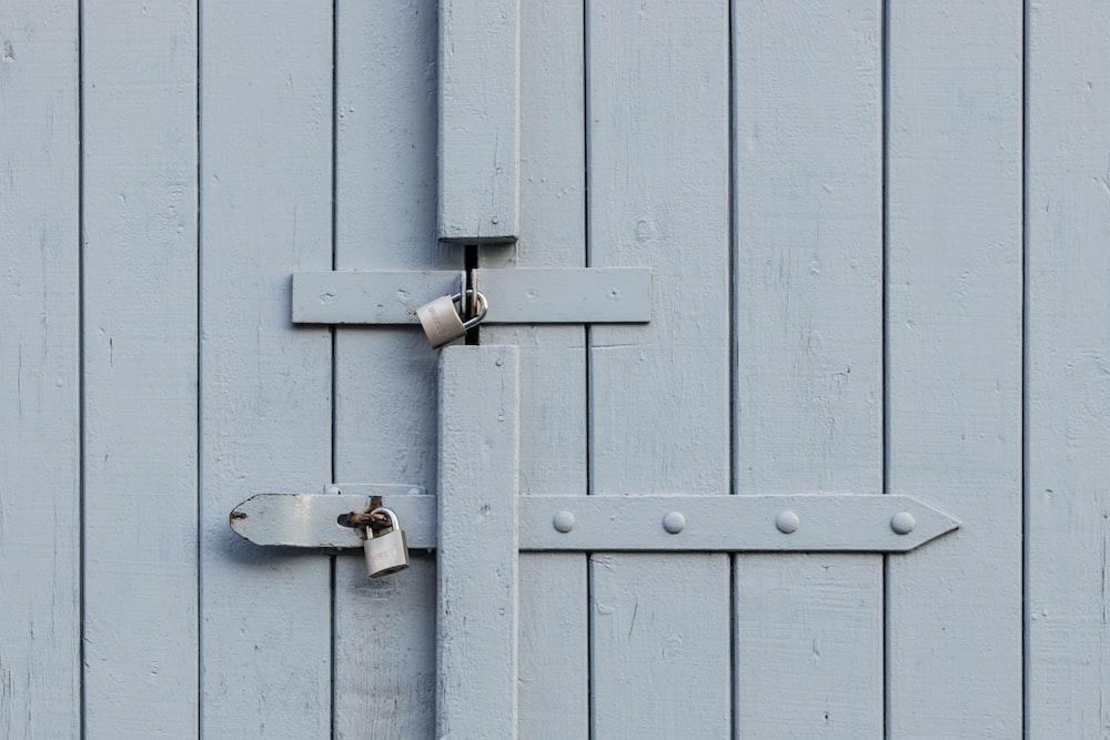 two gray metal padlocks on door