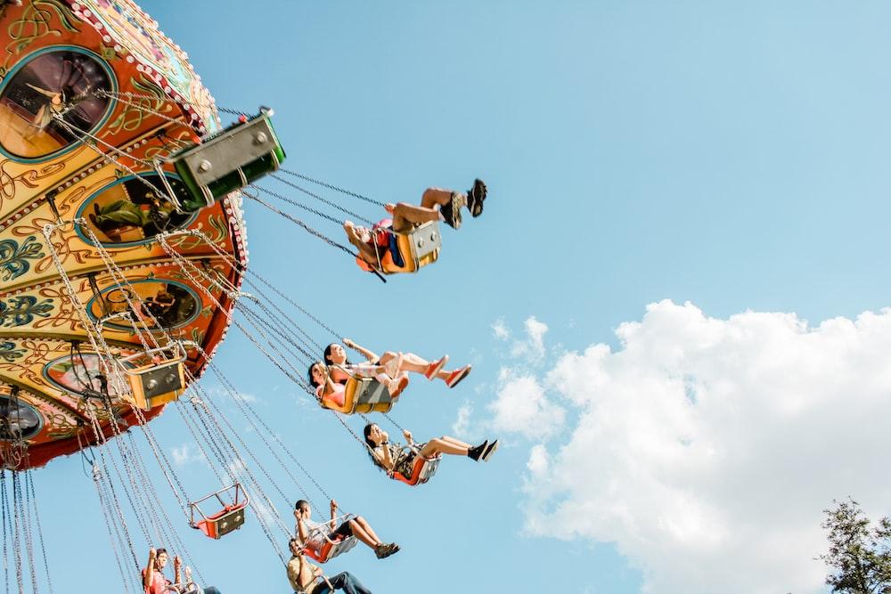 people riding on amusement rides at daytime