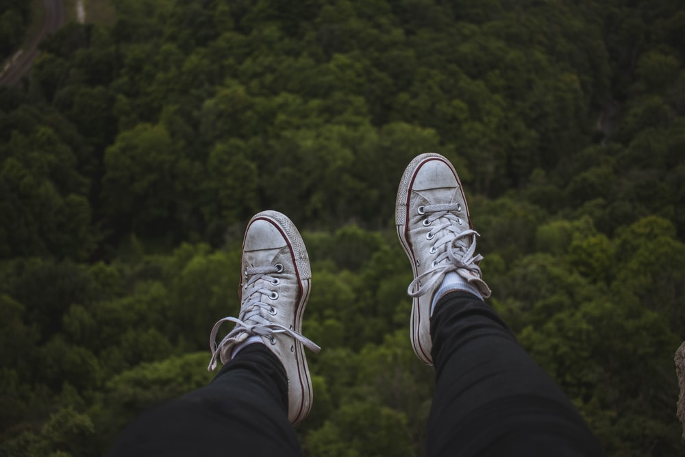 person sitting on cliff while wearing white shoes