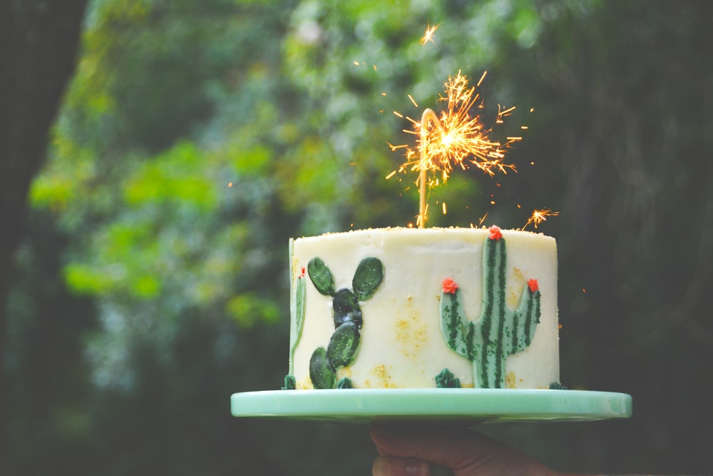 selective focus photograph of white and green cake with sparkler candle
