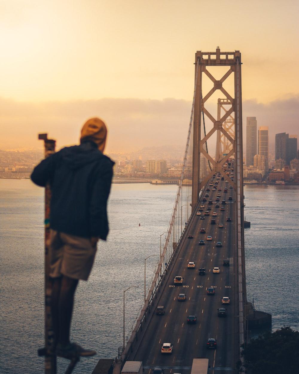man standing looking bridge