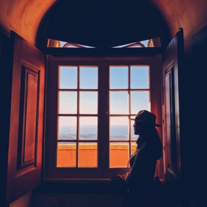 woman standing beside window