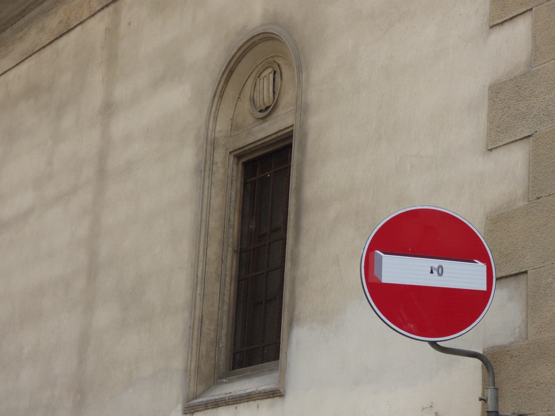 One of the unusual no entry roadsigns found in Florence Italy. Contrasting against the background of the building behind with an open window. It certainly  makes the no entry road sign a little less boring and plain