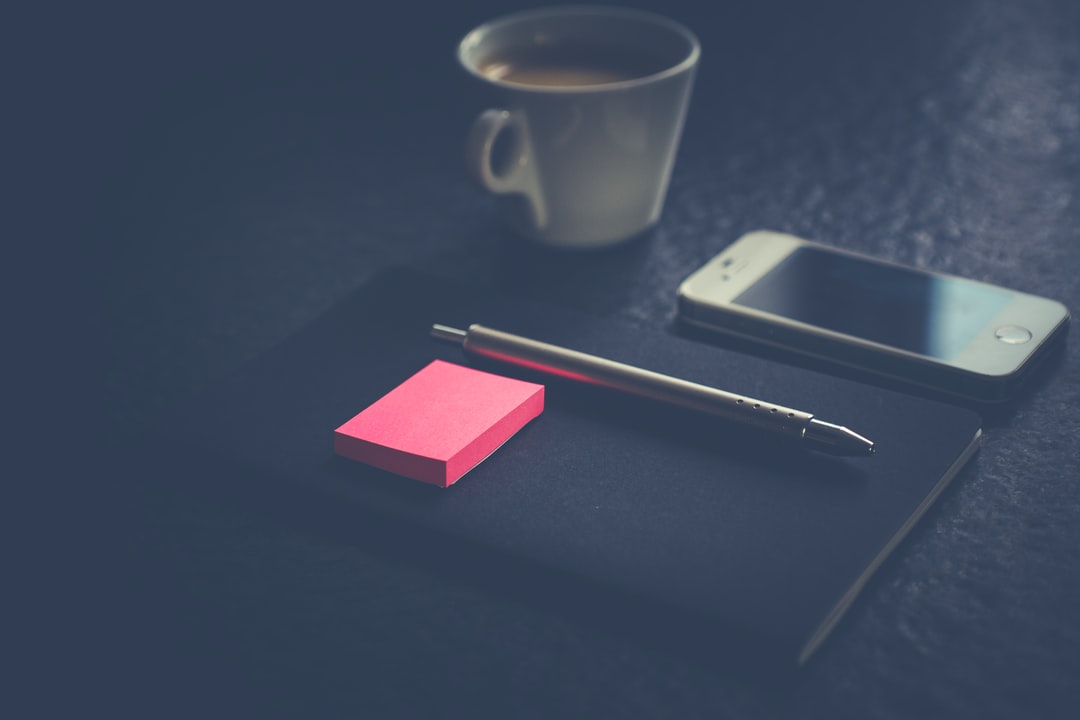 Black Minimalis Notebook, Sliver Pen, Smartphone, A Cup of Coffe and magenta Post-It