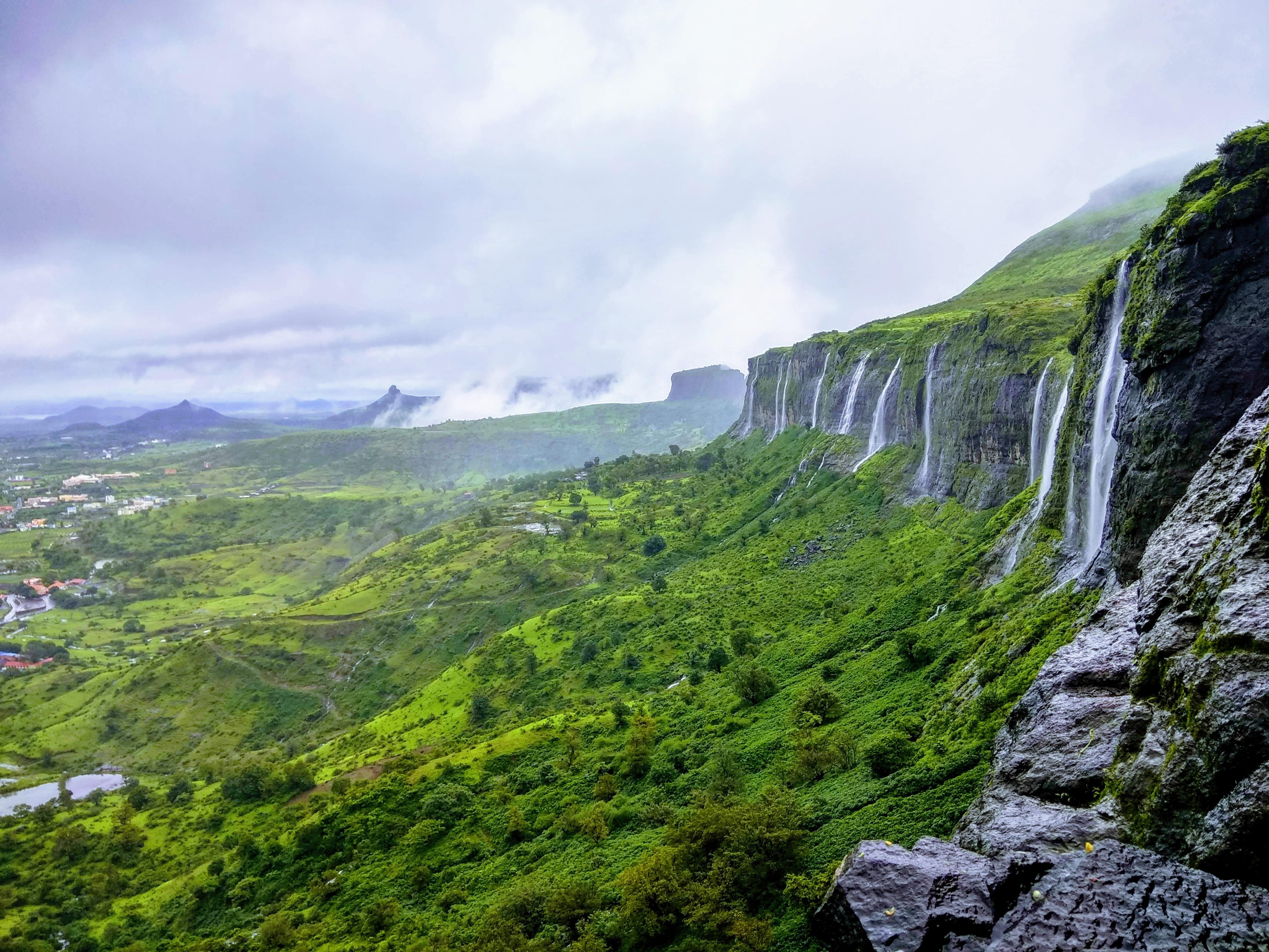 waterfalls on rock mountain during daytime