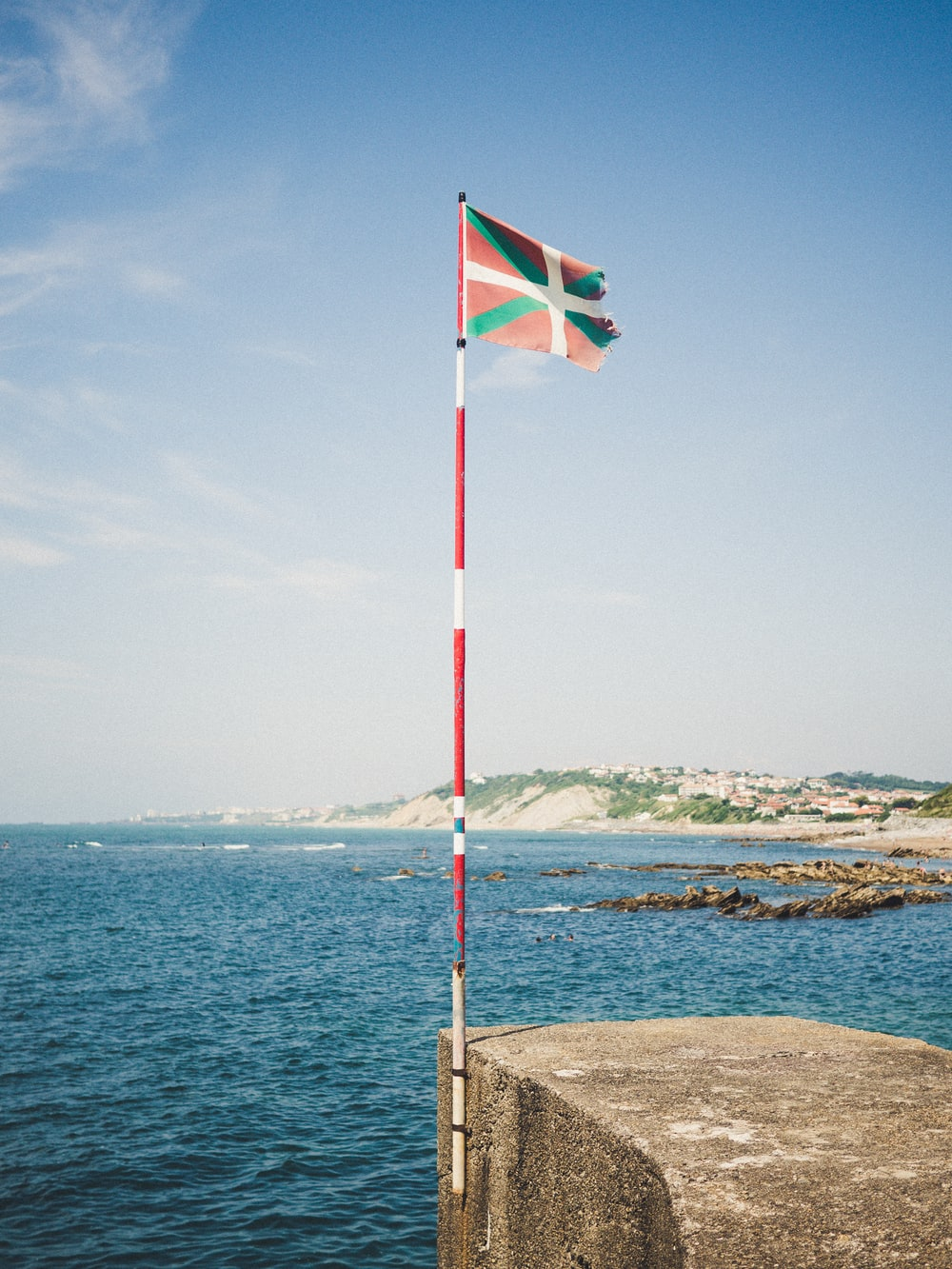 waving flag surrunded by body of water