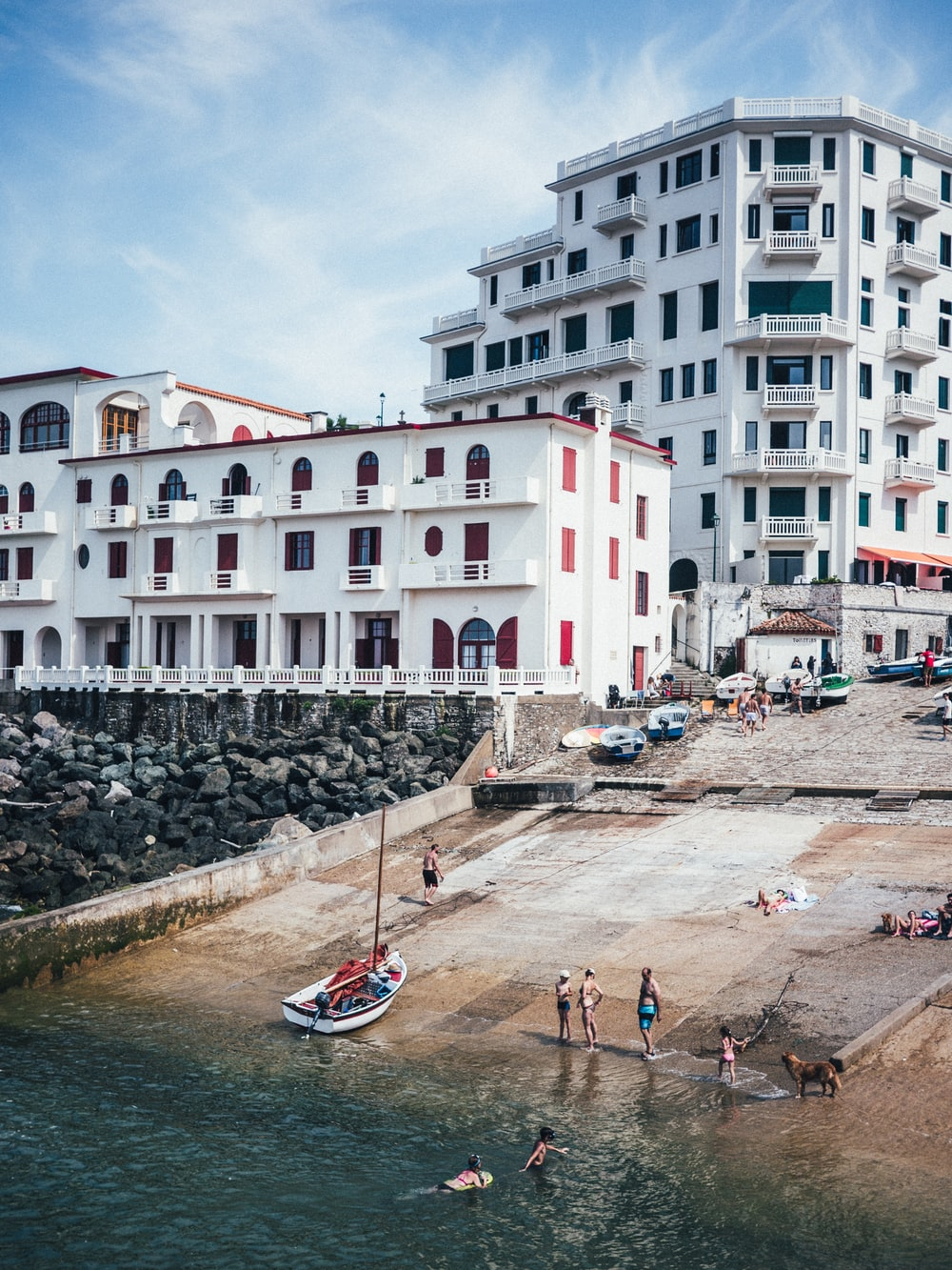 people by the beach near high rise buildings during daytime