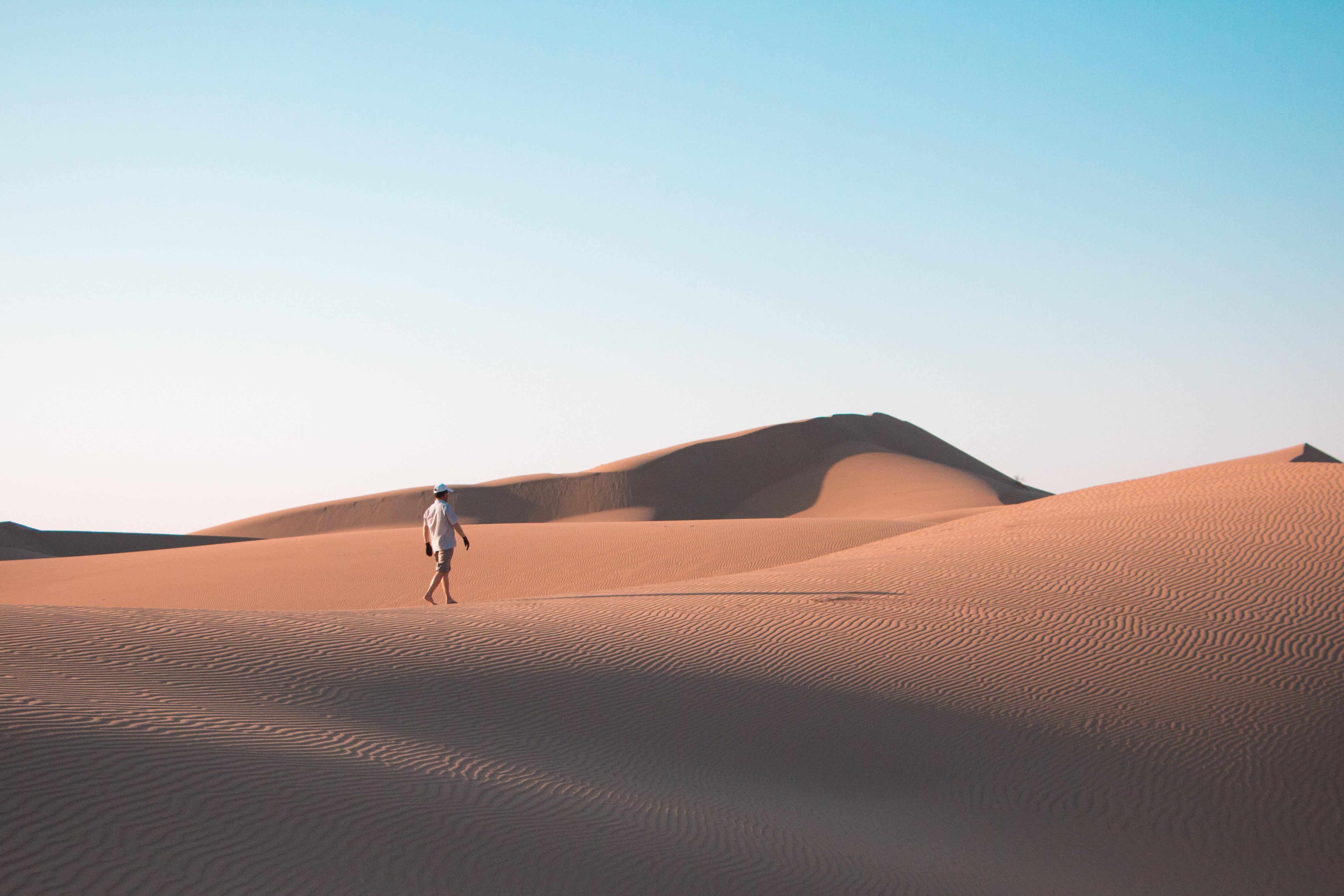 man walking on desert under blue sky during daytime