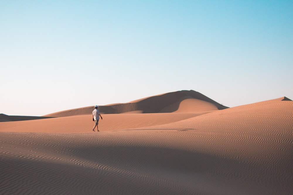 man walking on desert under blue sky during daytime