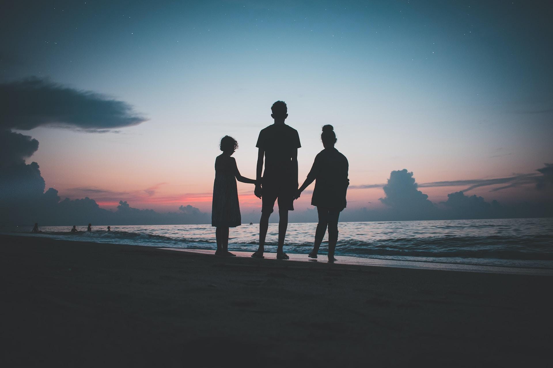 silhouette of three people walking beside body of water