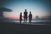 silhouette of three people walking beside body of water