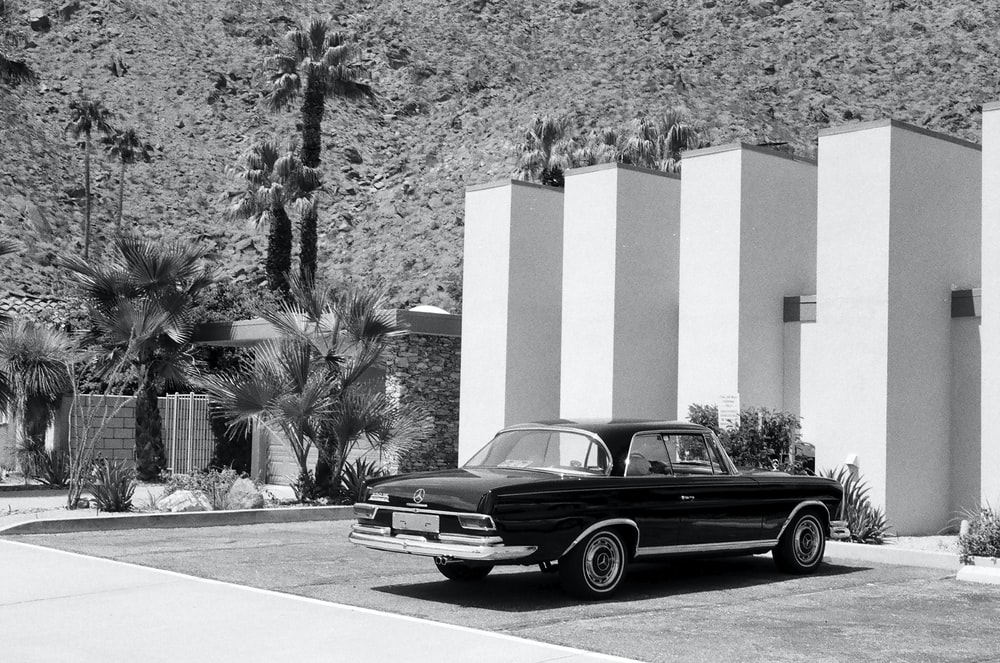 grayscale photography of gray coupe parked in front of white building