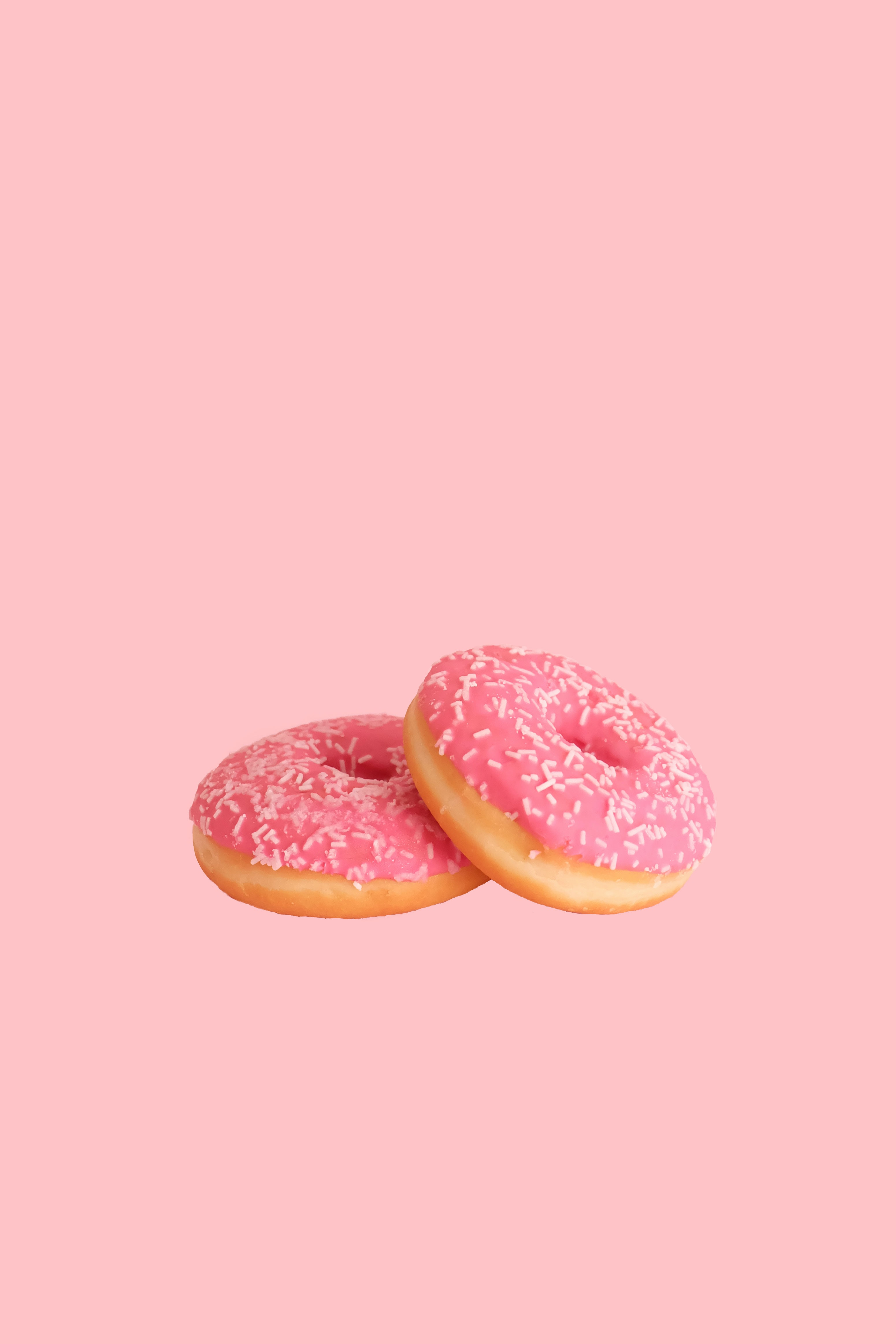 two strawberry doughnuts with sprinkles