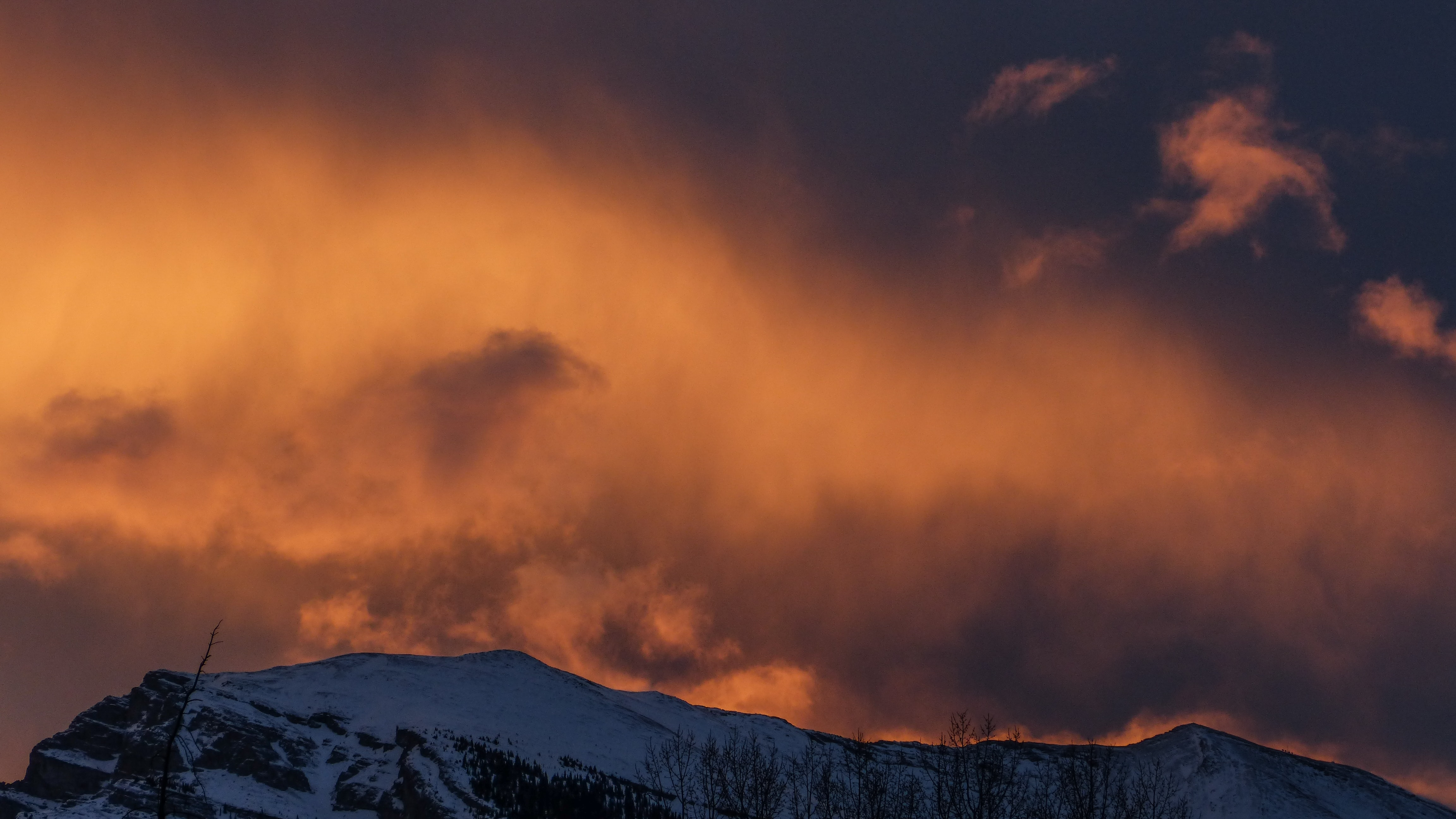 snowy mountain under cloudy sky during sunset