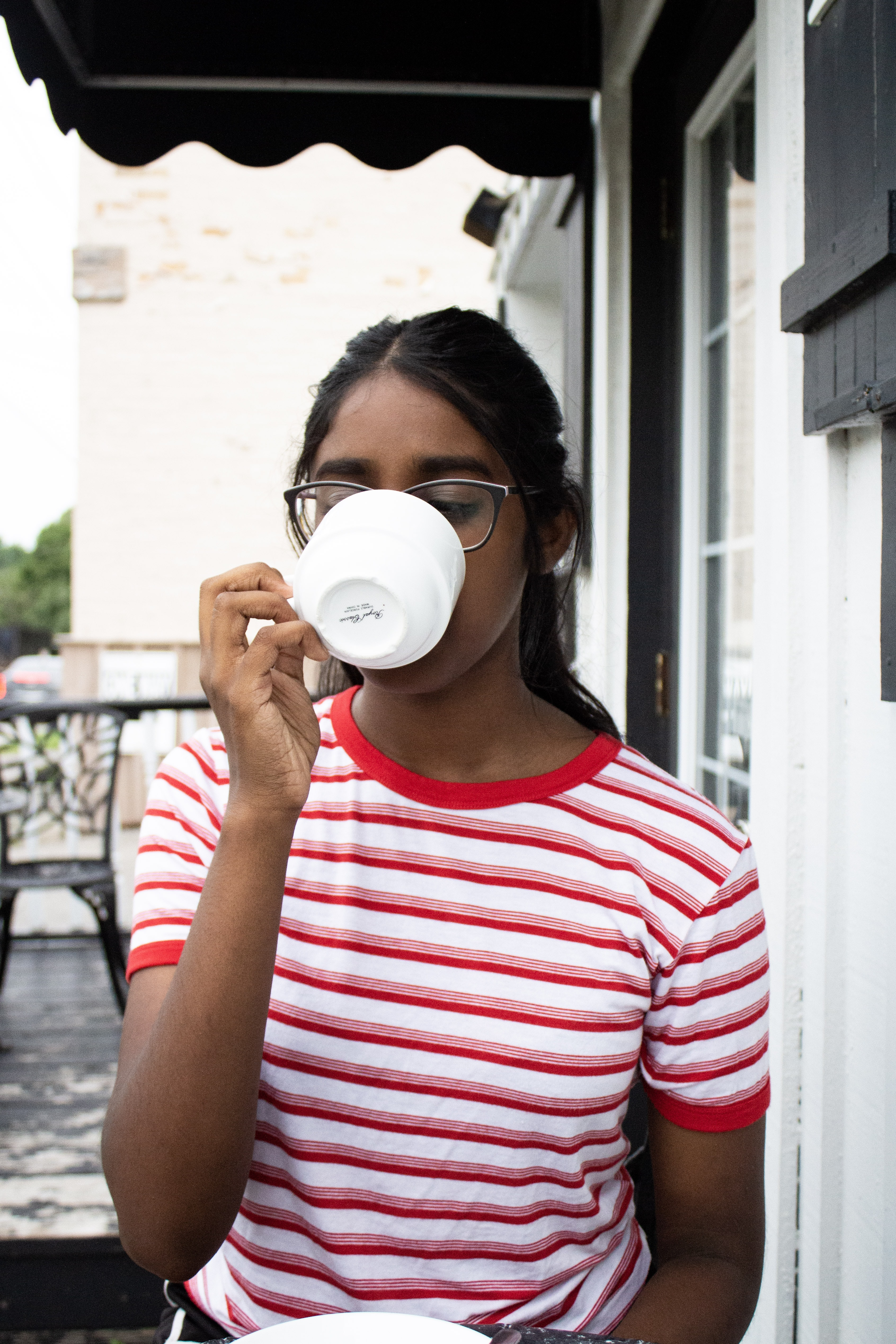 woman drinking coffee outside house