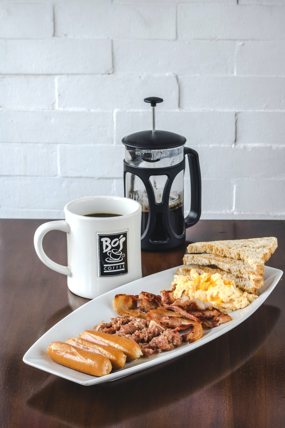 bread and bacon platter beside French press