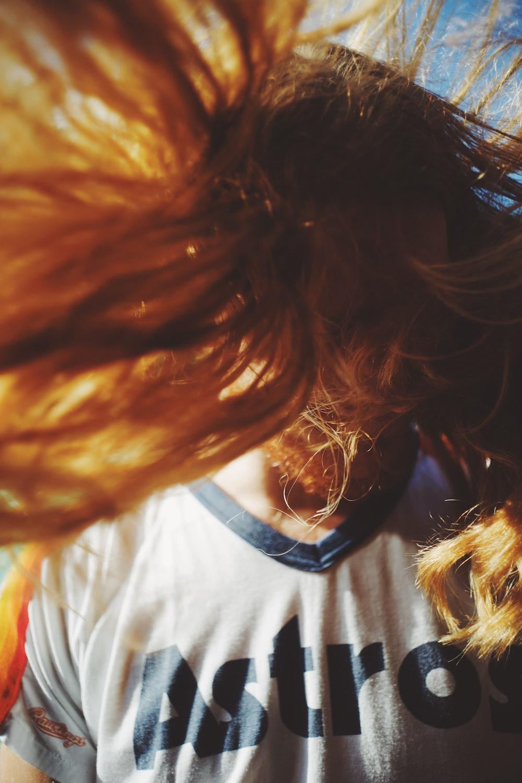 woman shaking her hair during daytime