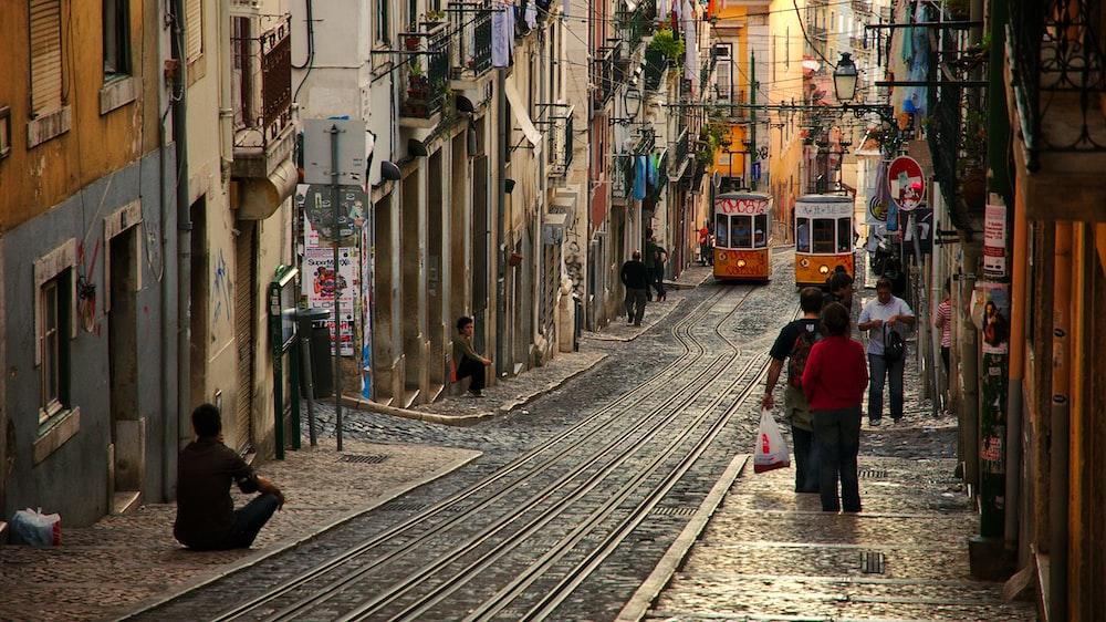 people walking on street near houses at daytime