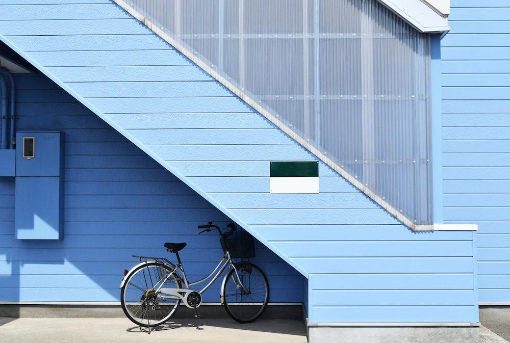 gray bike parked near blue house