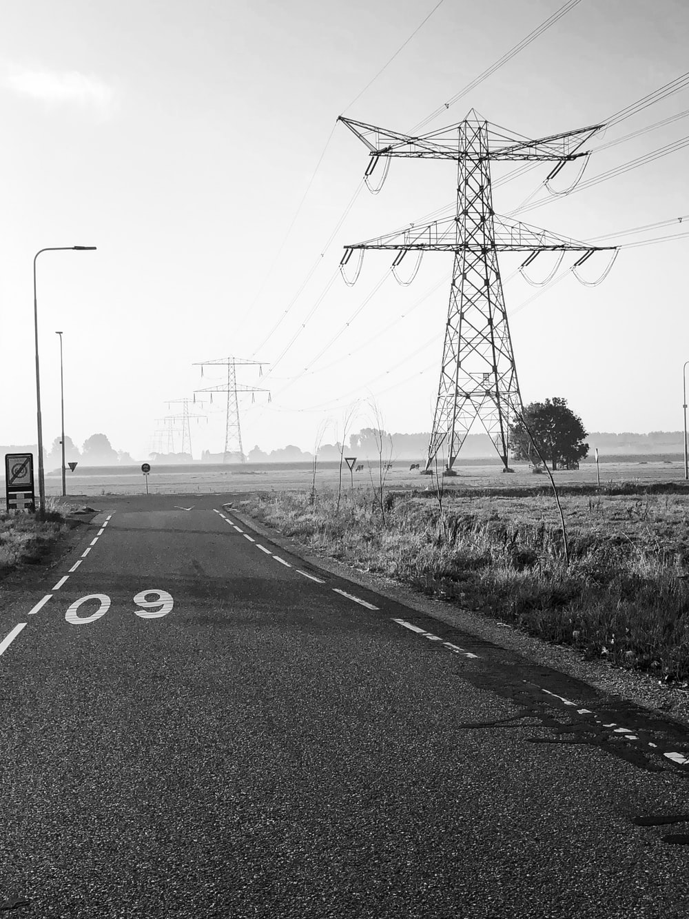 grayscale photography of road with utility tower