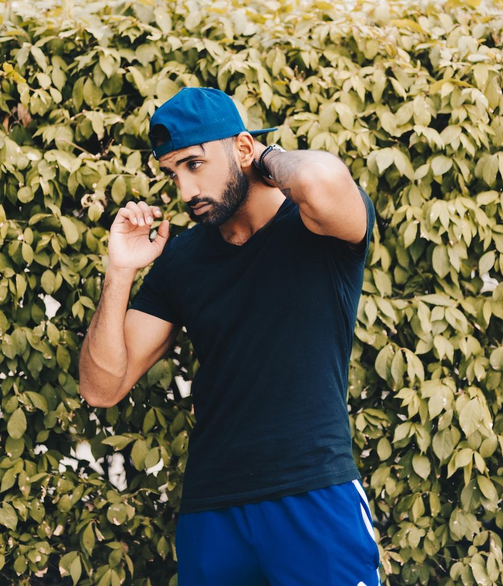 man wearing black V-neck t-shirt against green leafed wall