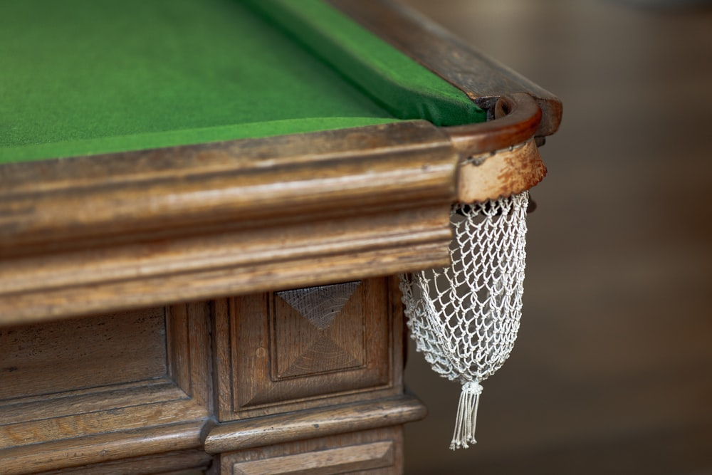 close up photography of green and brown pool table corner pocket