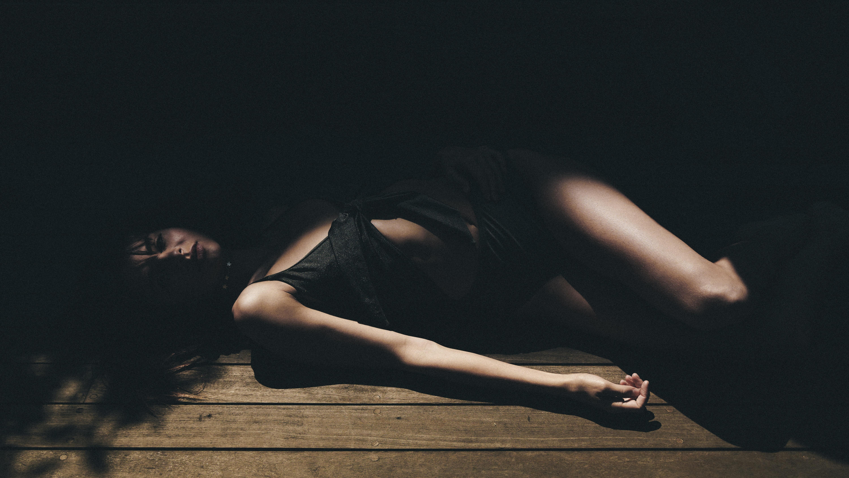 woman lying on brown wooden floor