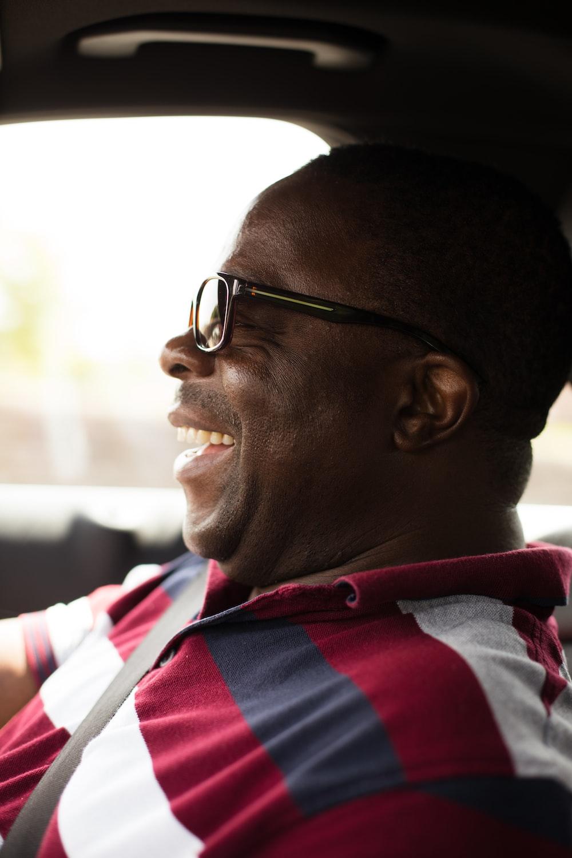 laughing man wearing eyeglasses inside vehicle