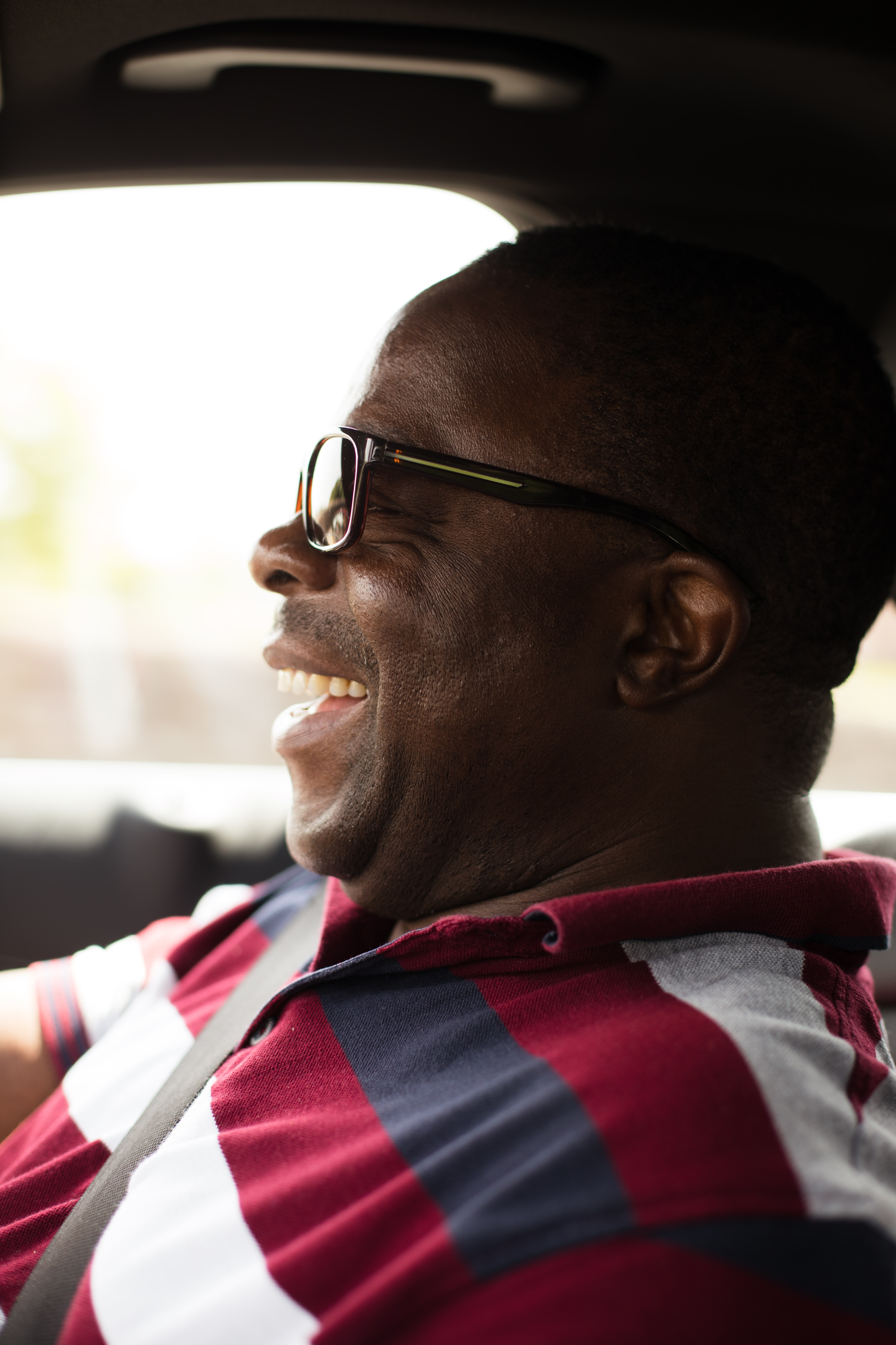 laughing man wearing eyeglasses inside vehicle