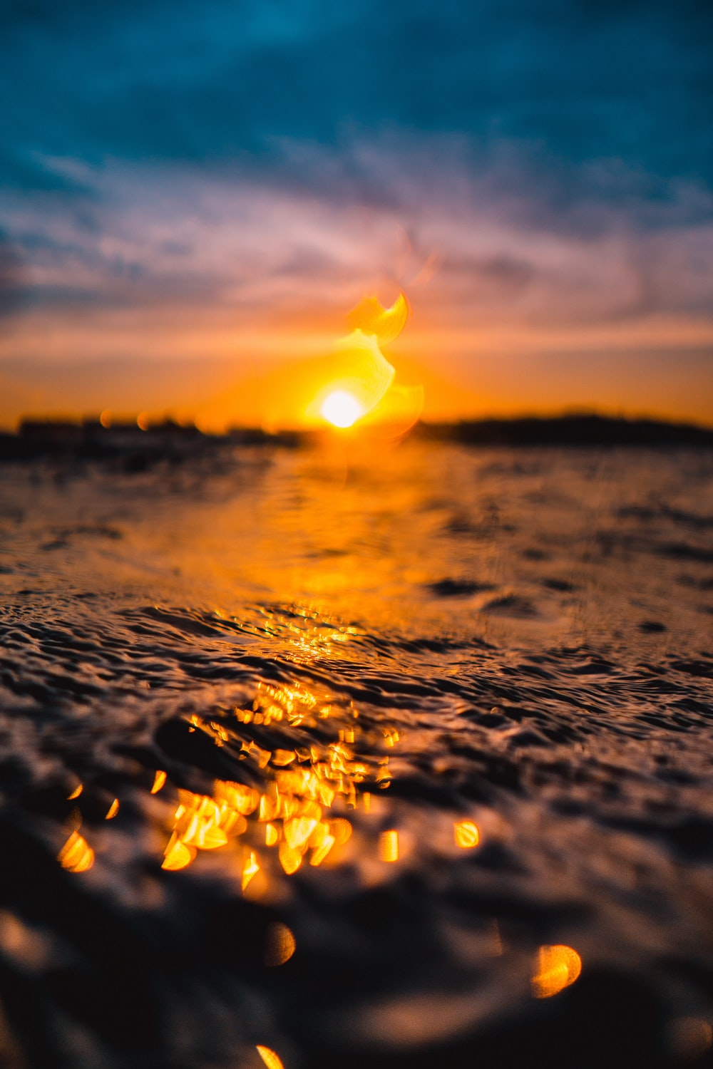 depth of field photography of body of water during golden hour