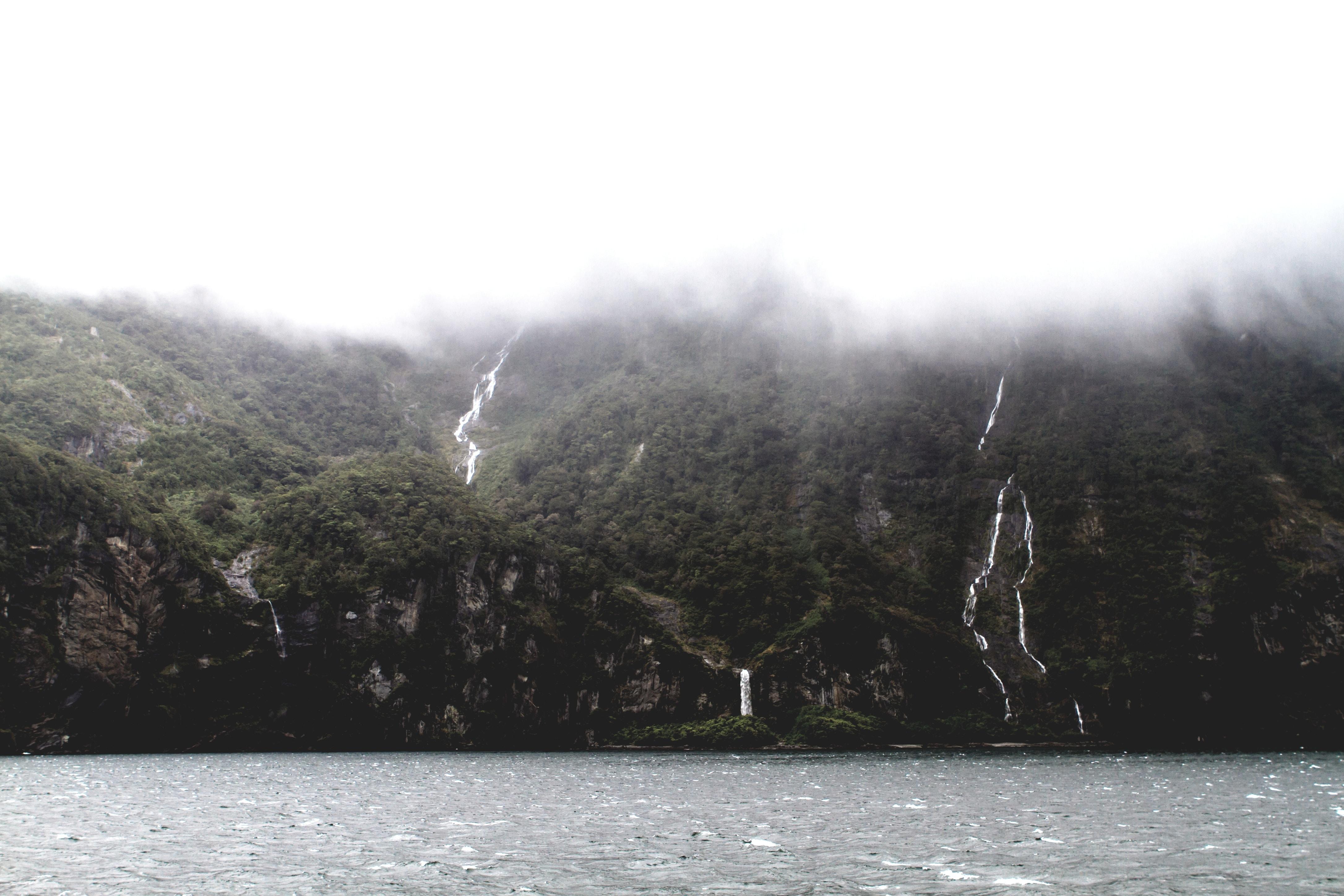 lake near waterfalls beside trees at daytime