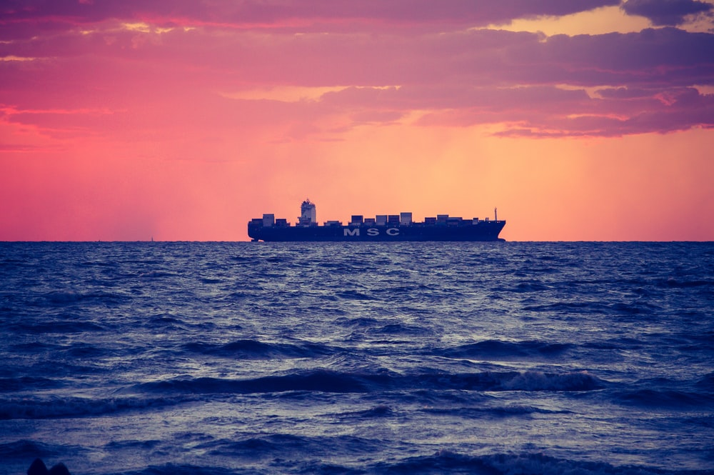 black ship on calm sea during golden hour
