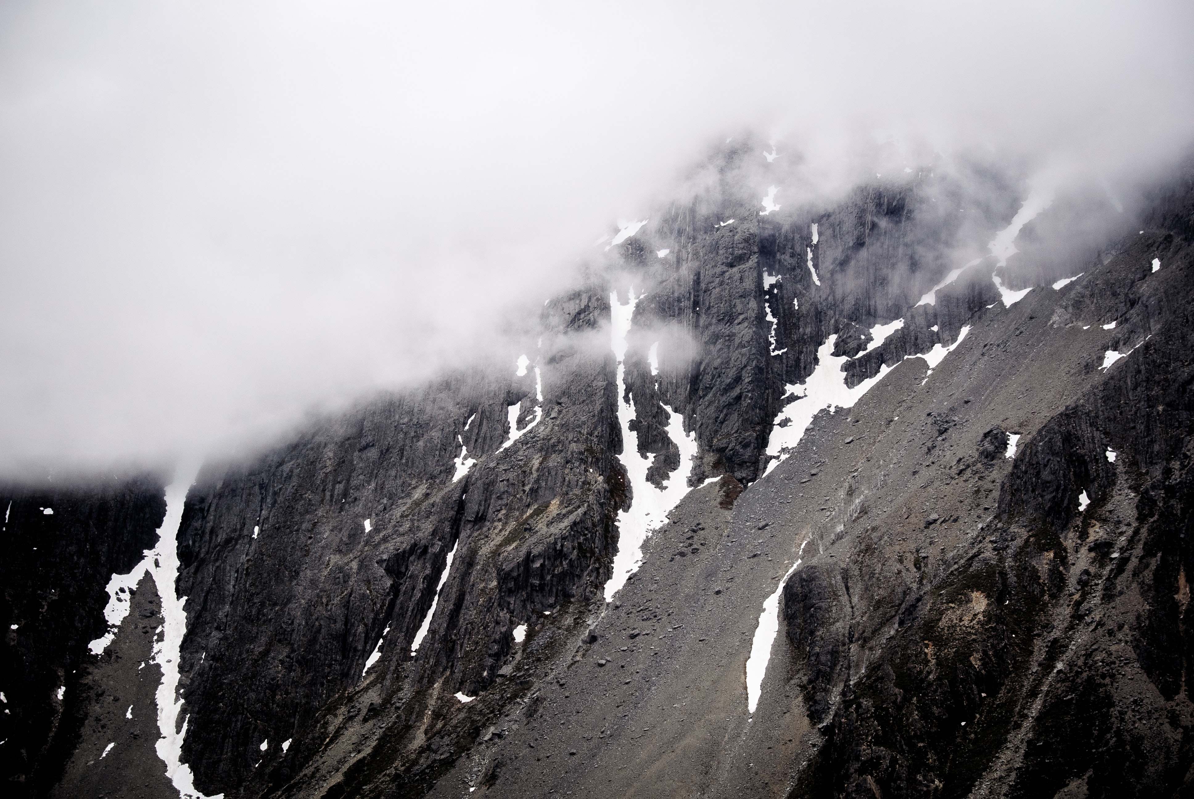 black and white mountain under cloudy sky