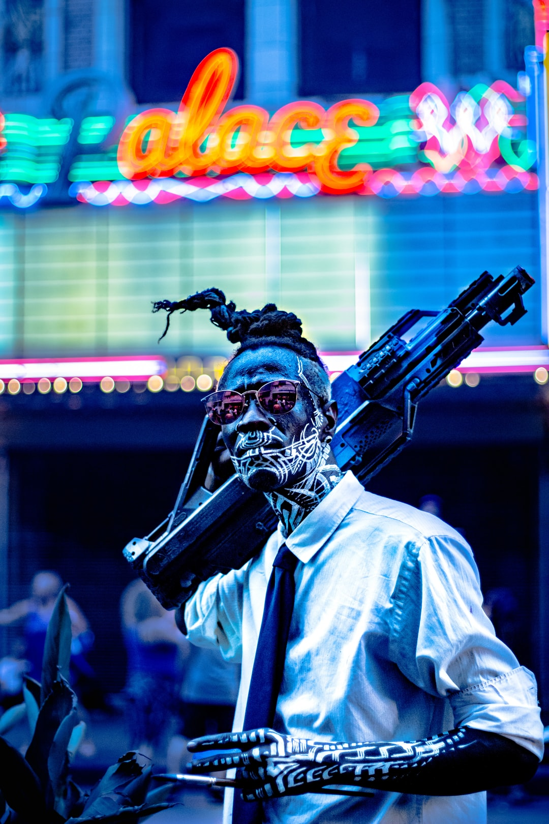 A dark-skinned man with intricate white tattoos, standing in front of a neon storefront with a futuristic gun resting nonchalantly over his shoulder.