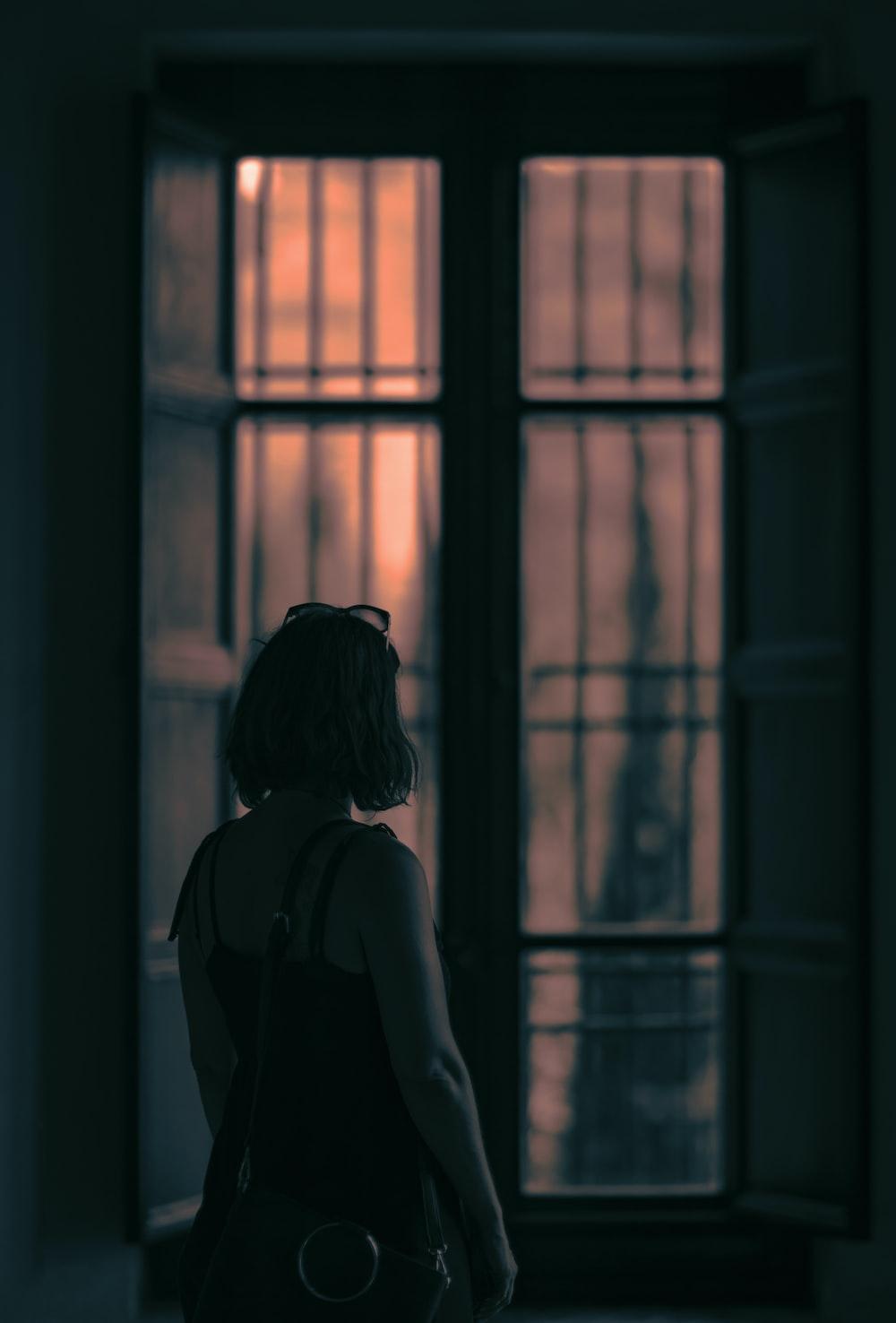 woman facing brown windowpane