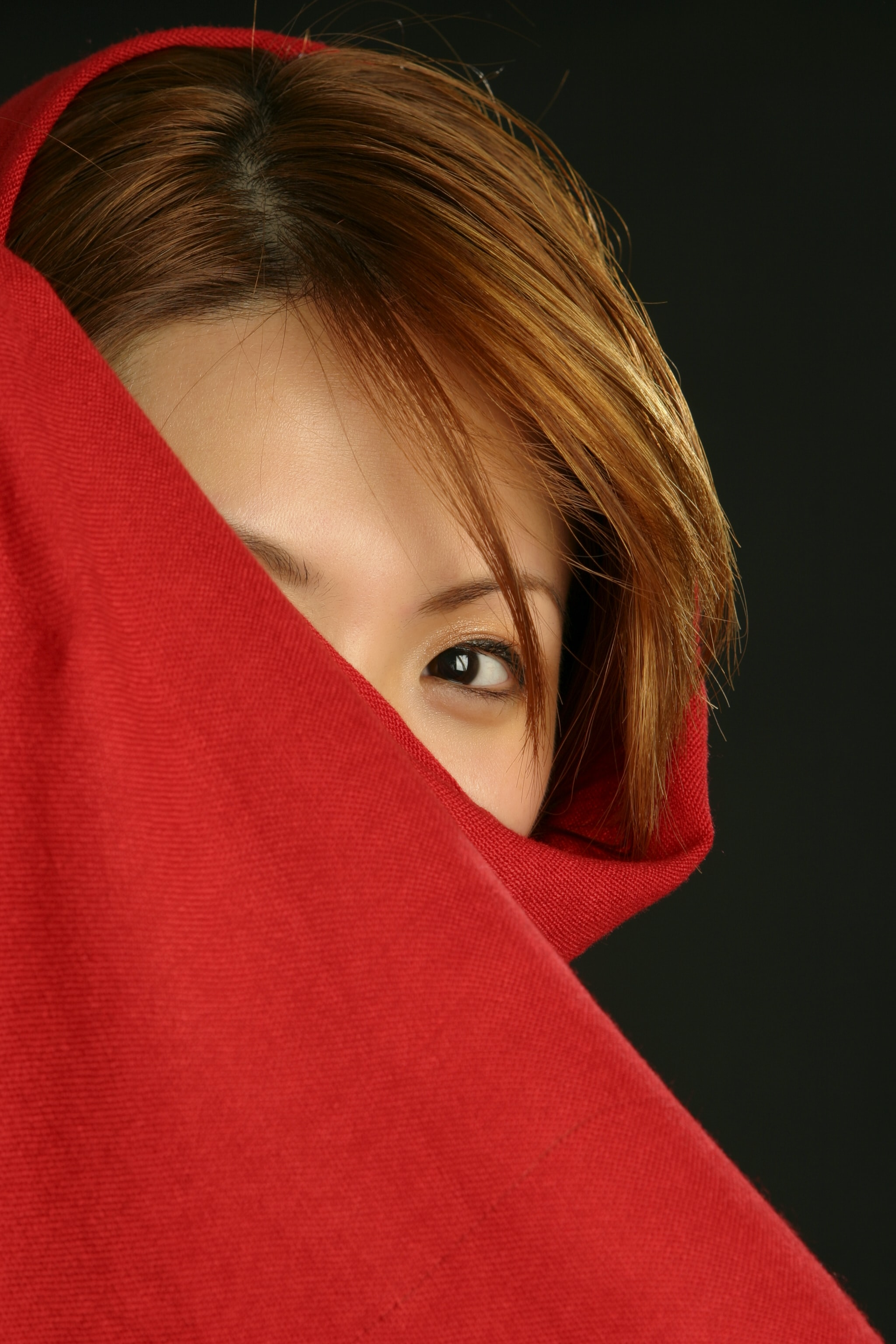 woman hiding in red textile