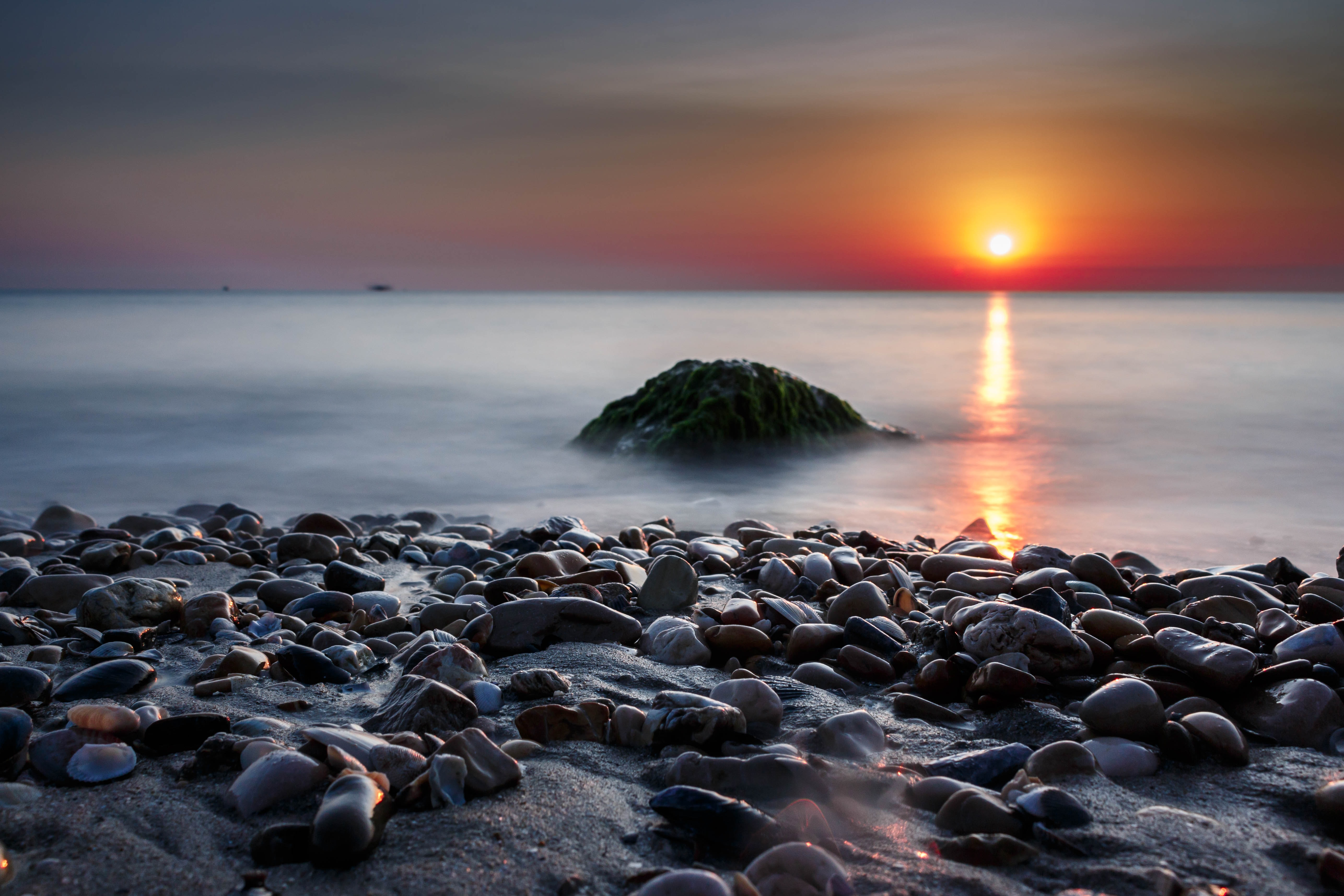 closeup photography of pebbles near ocean at golden hour