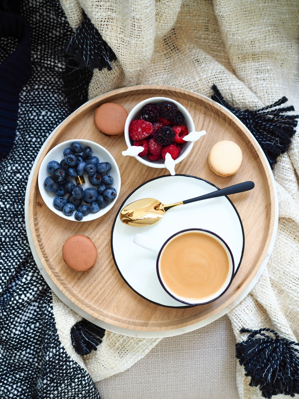 flat lay photography of cup of coffee beside raspberries and blueberries on bowls