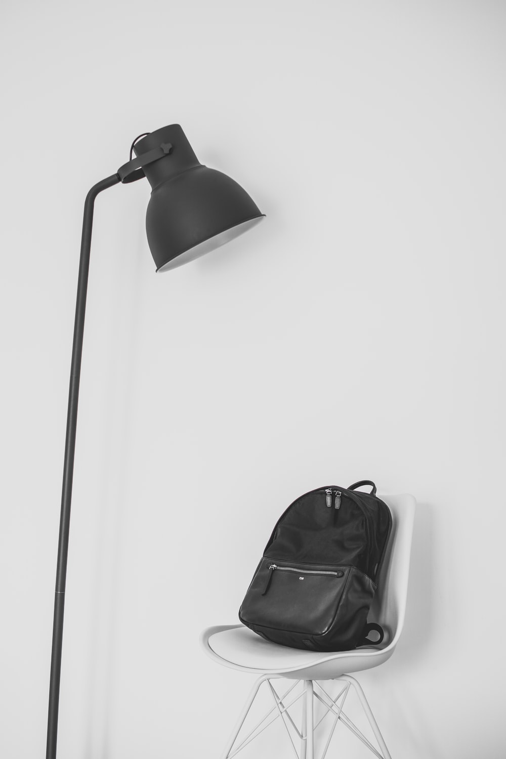 black lamp beside backpack on top of chair