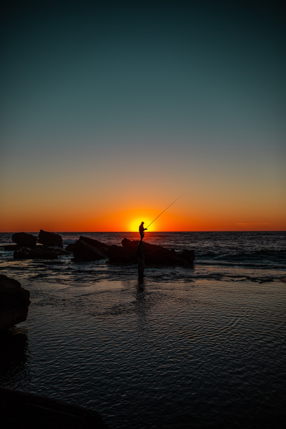 silhouette of man holding fishing rod