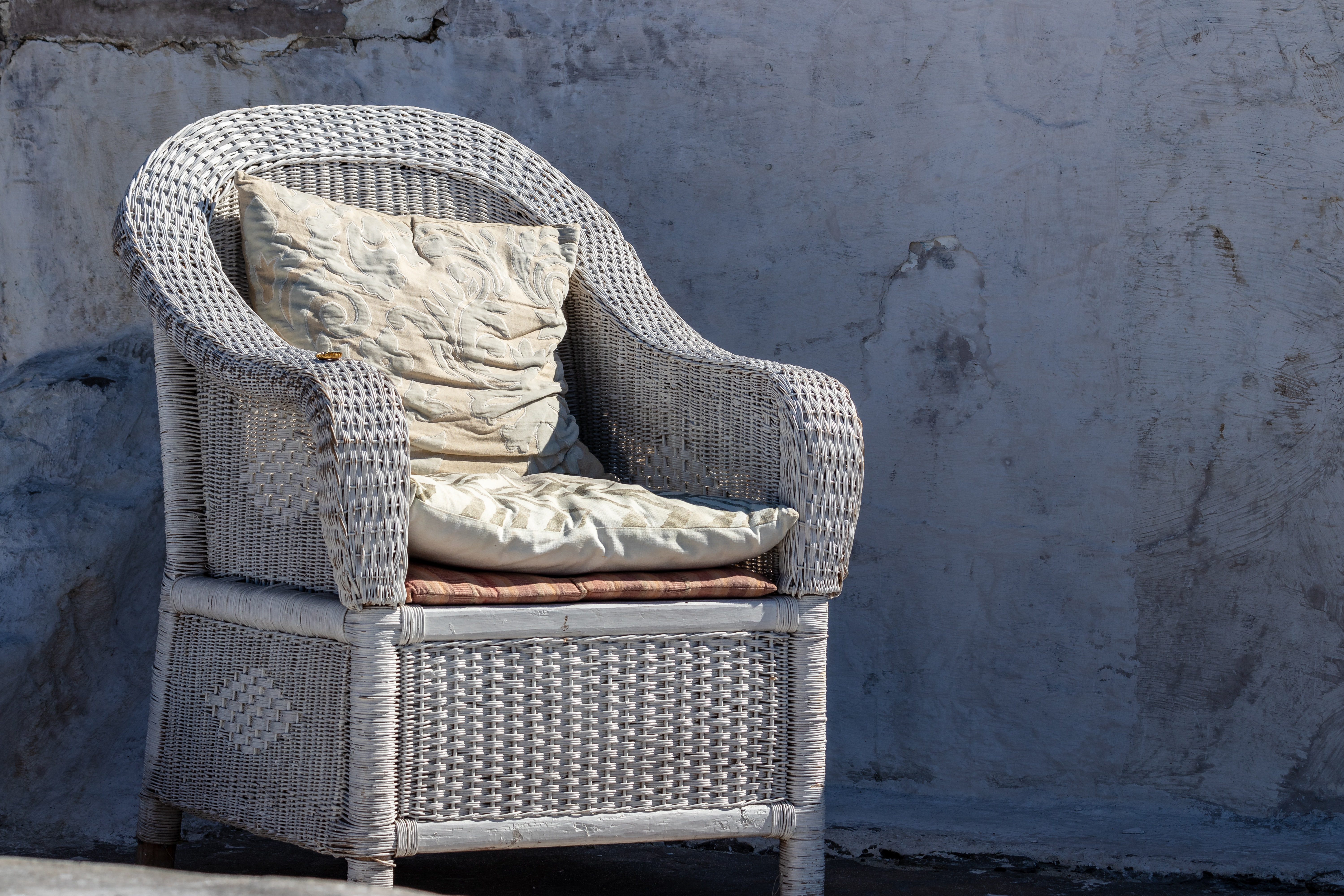 gray wicker armchair with gray cushion pads
