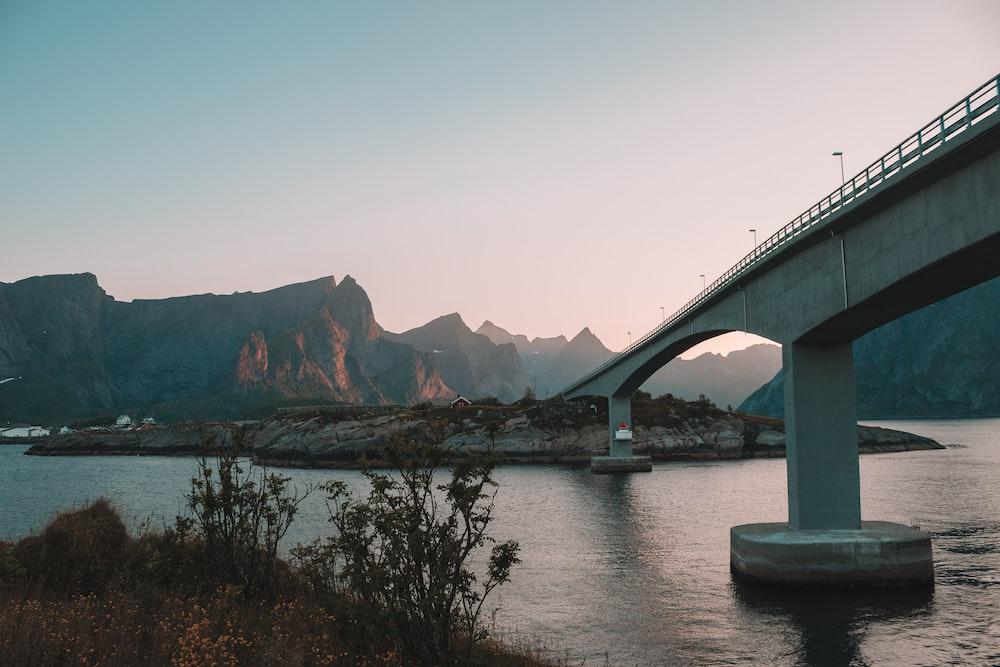 gray concrete bridge towards island