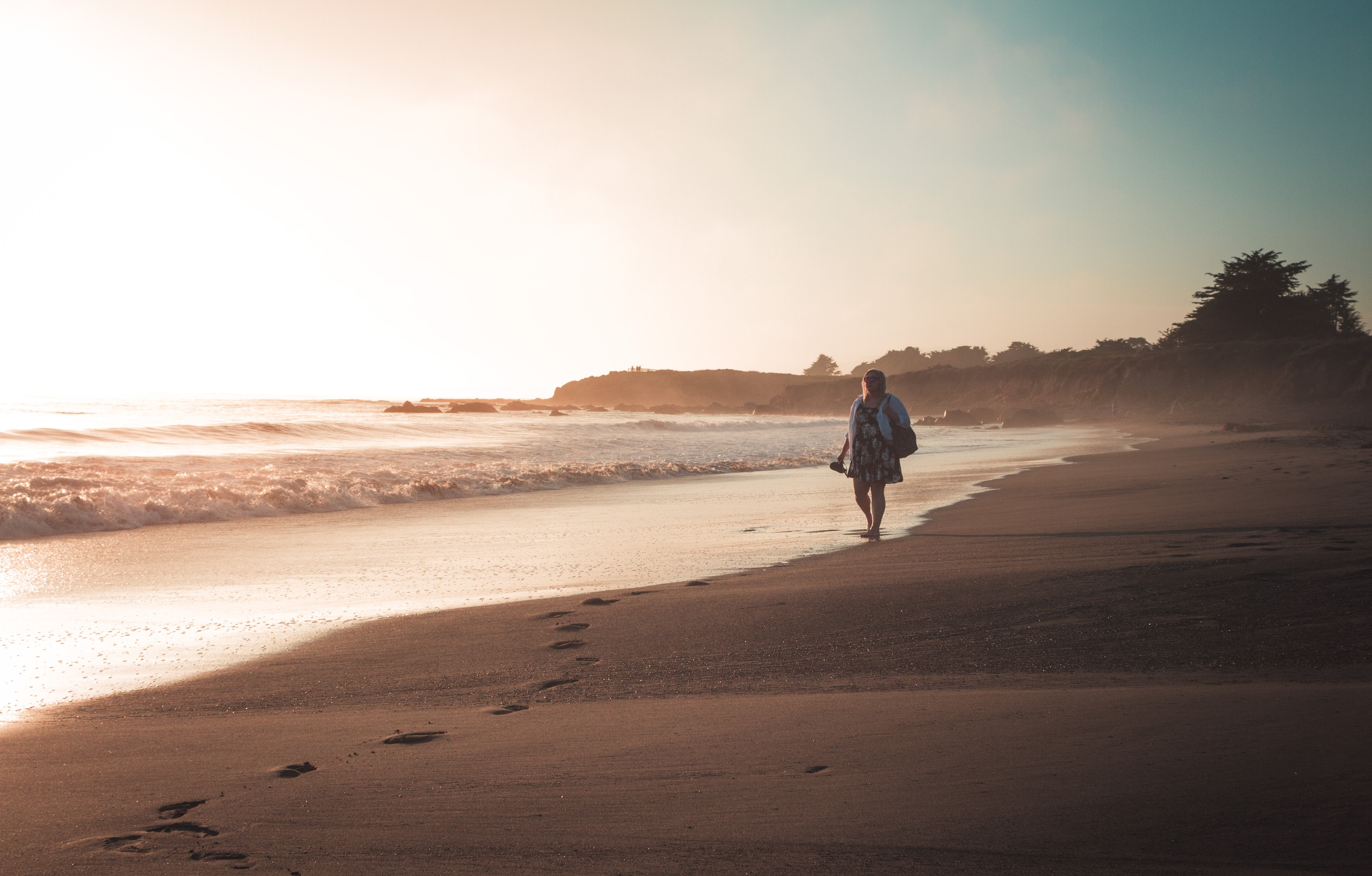 woman walking along the beach during daytime