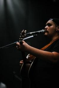 person playing guitar while singing