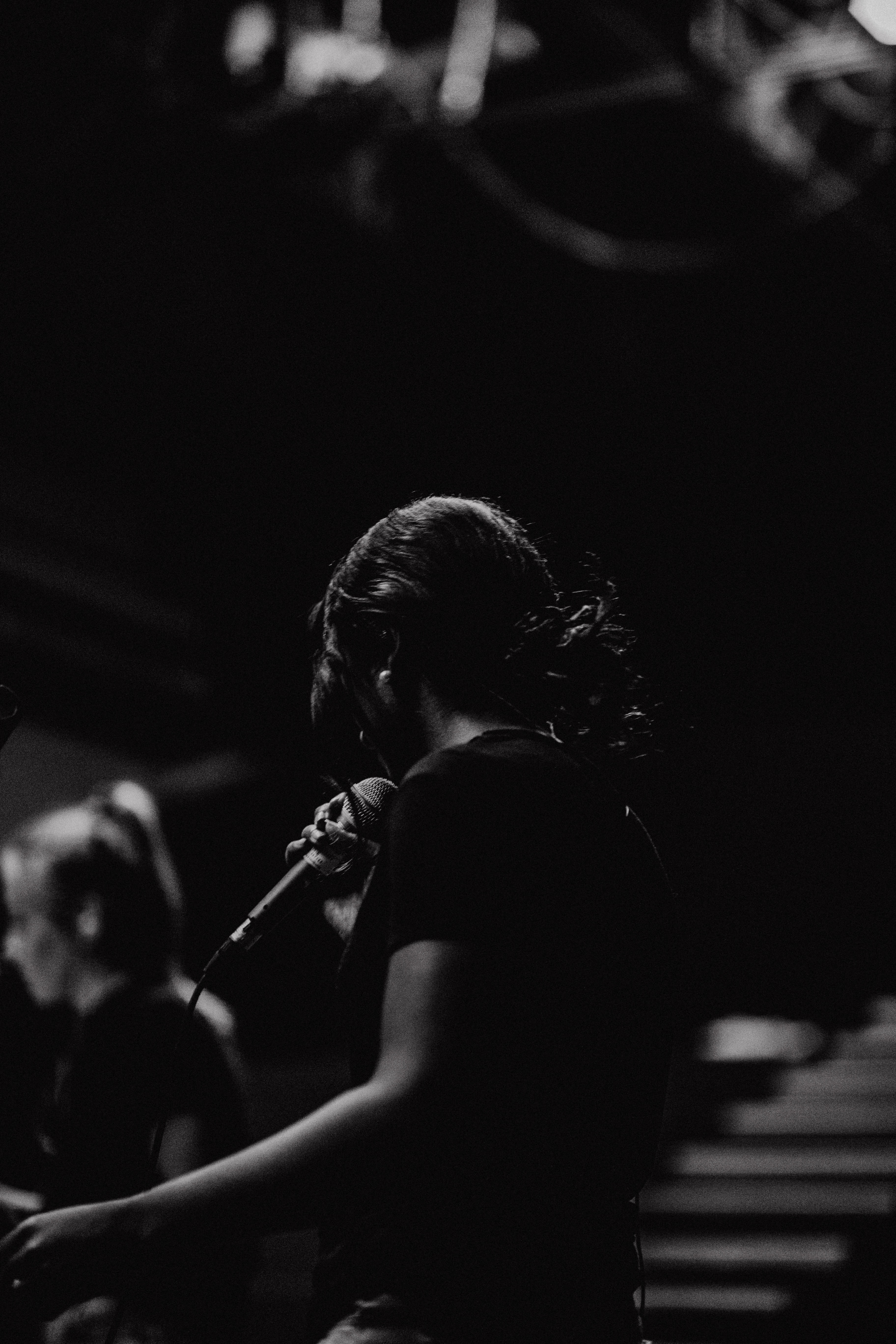 grayscale photography of person holding microphone