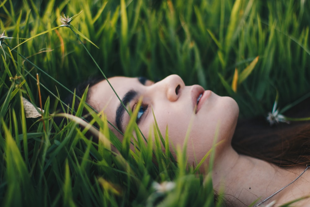 portrait photography of woman lying on grawss