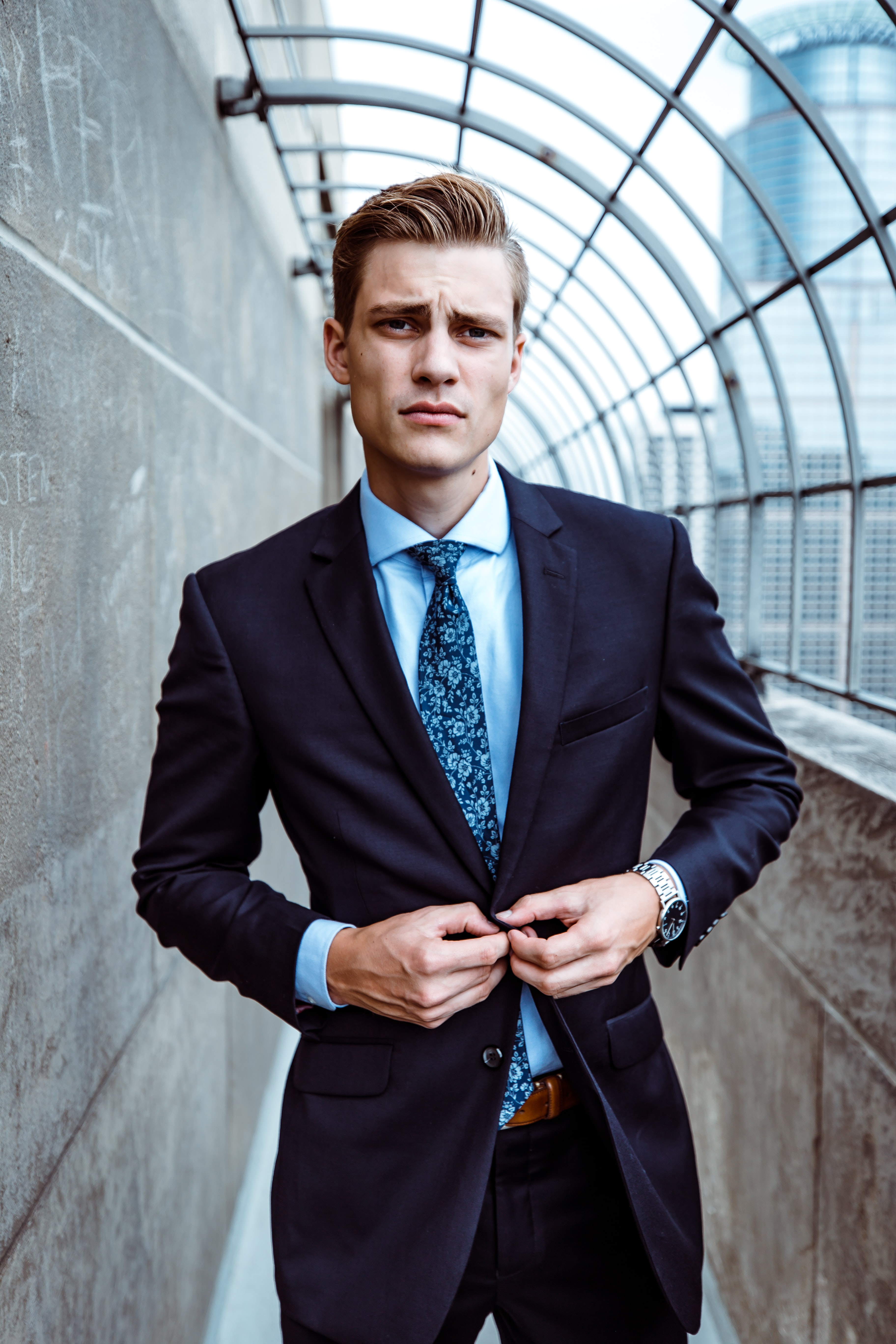 man wearing black and teal dress suit standing near gray wall