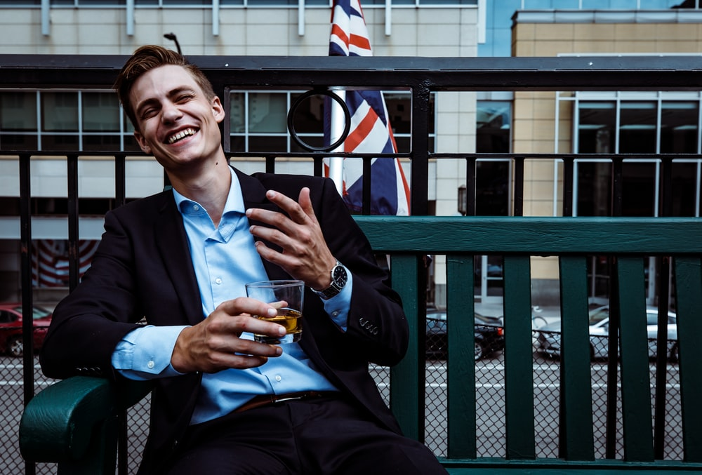 man smiling while sitting and holding whisky glass near concrete building