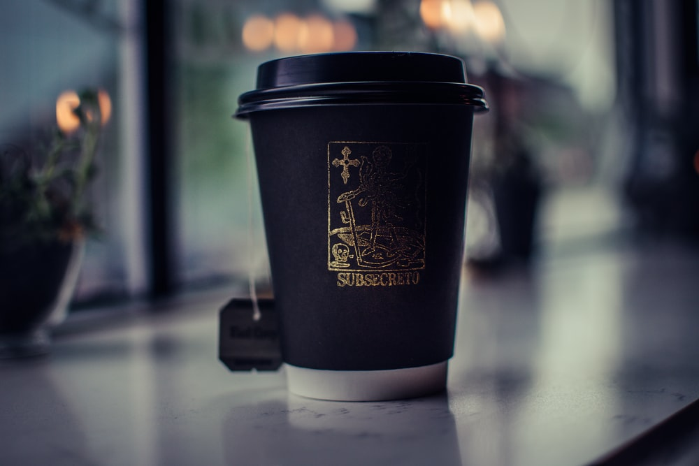 shallow focus photography of black coffee cup