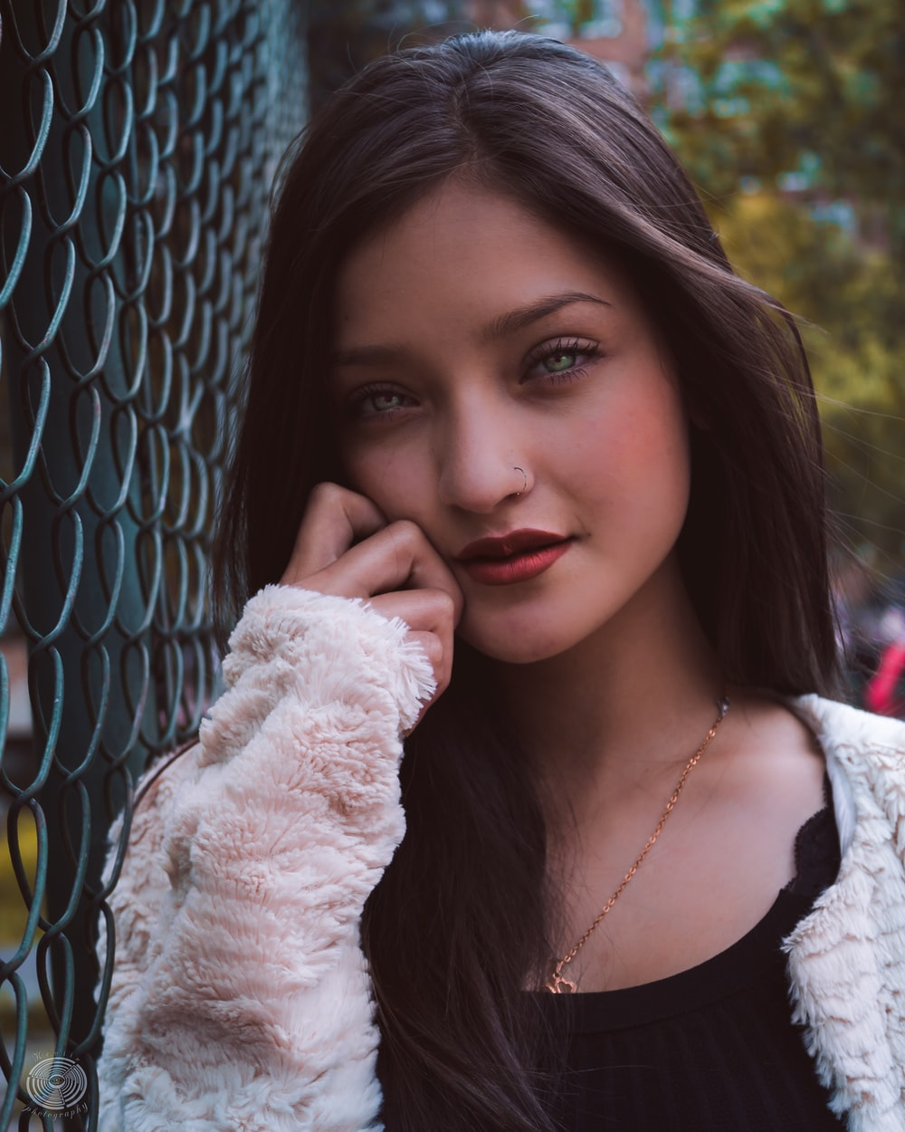 woman leaning on wire fence at daytime